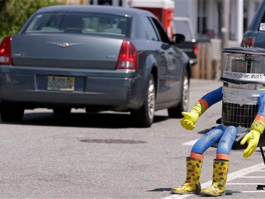 In this July 17, 2015, file photo, a car drives by HitchBOT, a hitchhiking robot in Marblehead, Mass. The Canadian researchers who created hitchBOT as a social experiment say someone in Philadelphia damaged the robot beyond repair on Saturday, Aug. 1, ending its brief American tour. The robot was trying to travel cross-country after successfully hitchhiking across Canada last year and parts of Europe.