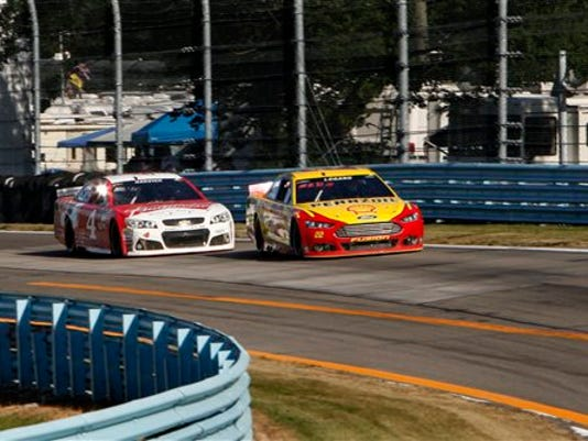 Joey Logano (22) passes Kevin Harvick (4) coming into the last turn on the way to winning a NASCAR Sprint Cup series auto race at Watkins Glen International, Sunday, Aug. 9, 2015, in Watkins Glen, N.Y.