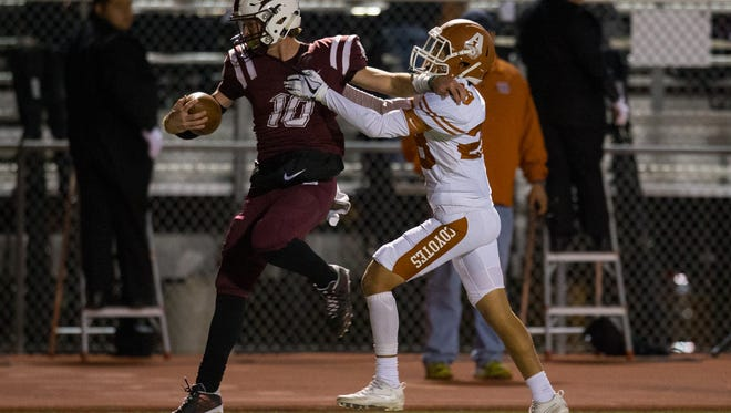 Calallen's quarterback Colten Duff is pushed out of bounds by Alice's Miguel Gonzalez as he runs the ball for a first down during the first quarter of their game at Wildcat Stadium on Friday, Oct. 27, 2017