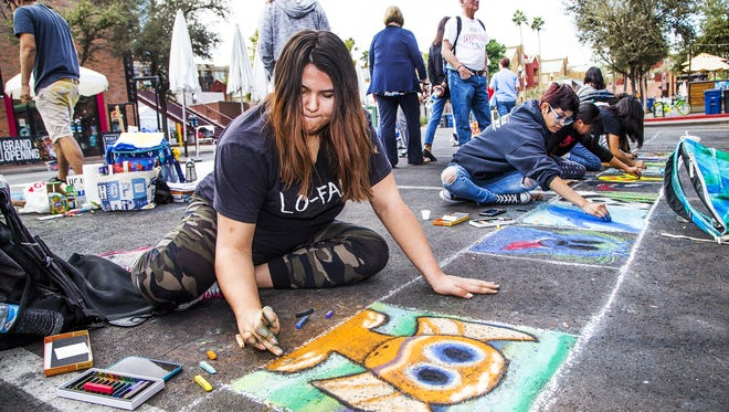 Acacia Raley, 19, Phoenix, a student at Arizona State University, tries her hand at sidewalk chalk painting at the Tempe Festival of the Arts, Friday, December 1, 2017.