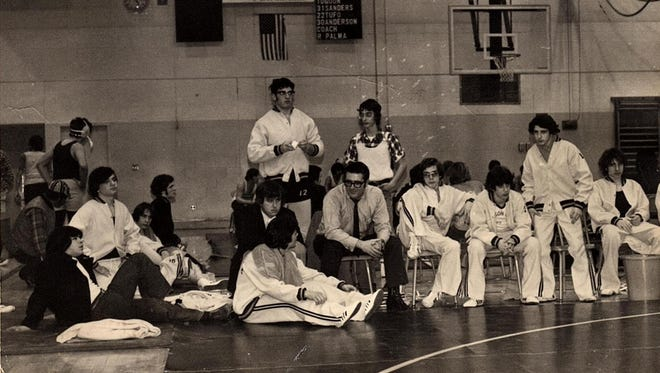 Wrestling coach Jim Silvestri (seated, center) sharing a light moment during a 1975 match at Belleville.