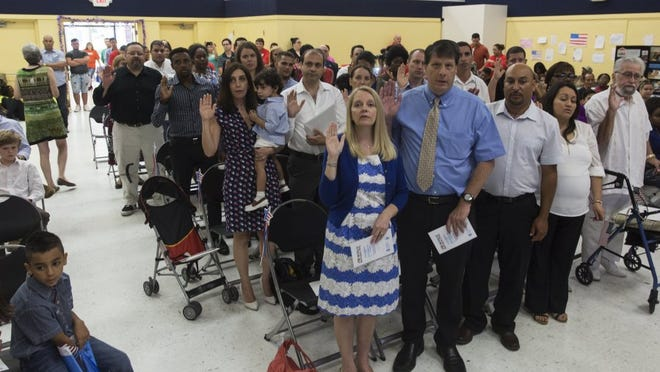 Twenty-nine refugees from 11 countries are sworn in during the citizenship ceremony on World Refugee Day at Golden Gate Community Center on June 25, 2016, in Golden Gate.