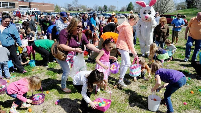 Photos by MIKE LAWRENCE / COURIER & PRESS The Easter bunny watches as hundreds of Easter egg hunters scour the ground behind Evansville's Mater Dei High School for Saturday's West Side Nut Club Easter Egg Hunt Saturday.