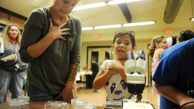 Jessica Nagashima and her daughter, Ariah Nagashima, 7, react to looking at a large bug under the Microscope at Bug Fest at Wesselman Woods Nature Center in 2014. Ariah does not like bugs but her family came to learn about different types of bugs and why they are essential part of the ecosystem.