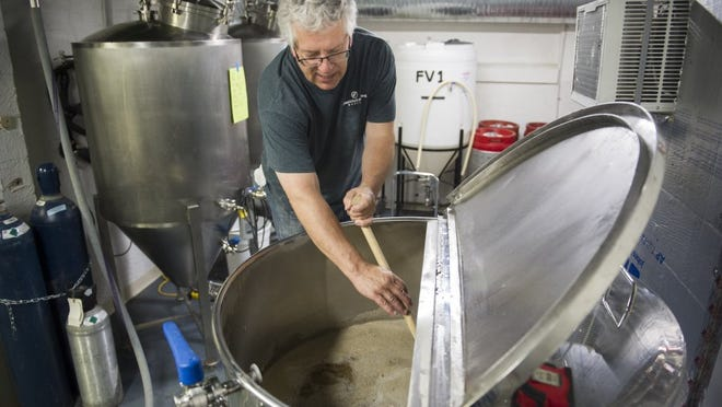 "ALEX SLITZ / COURIER & PRESS Jeff Smith, of Evansville, stirs a tank of Skinny Blonde, a golden ale style beer, at the Evansville Brewhouse in Evansville, soon after they opened. Smith has been brewing beer since 2009. ""Theres a lot of D.I.Y. in this brewery,"" he said."