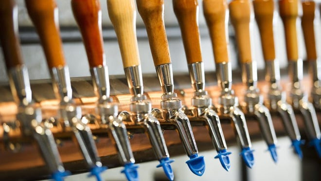 ALEX SLITZ / COURIER & PRESS Beer tap handles sit above the bar at the Evansville Brewhouse in Evansville.