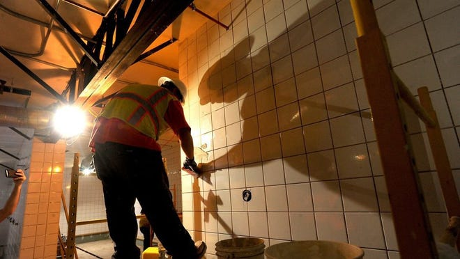 ROB VARELA/THE STAR Angel Hernandez grouts the tile in the shower room at the Rams practice facilities on the campus of CLU in Thousand Oaks.