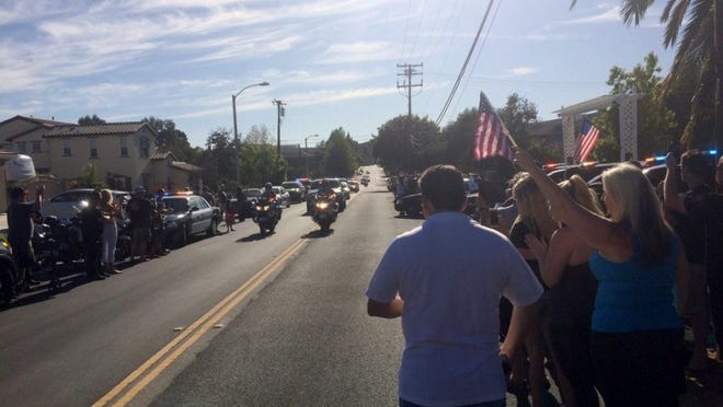CONTRIBUTED PHOTO/SIMI VALLEY POLICE DEPARTMENT Simi Valley police Officer Tom Carney, who was injured in a traffic accident last month, was welcomed home from the hospital Friday by friends, neighbors and local law enforcement and fire officials.
