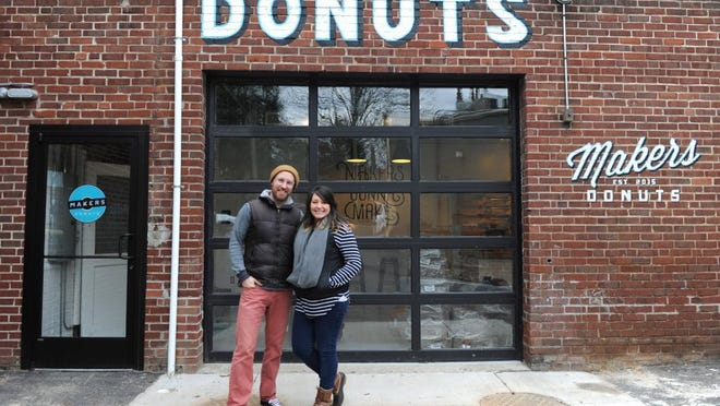 Sara and Sean Alsobrooks stand outside their Makers Donuts shop on Tyson Street.