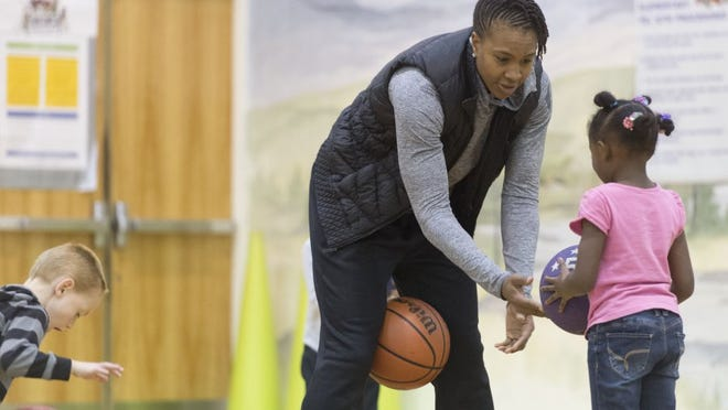Tamika Catchings helps B'Lana Perry with her ball handling at Woodland Elementary School in Oak Ridge on Monday, December 8, 2015. Catchings was at the school to promote Champions for America's Future's report regarding the importance physical education in schools. (SAUL YOUNG/NEWS SENTINEL) B'Lana Perry