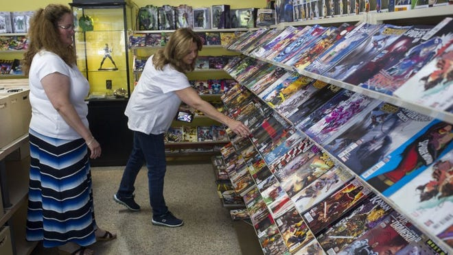 The Golden Age comic book store co-owner Stephanie Laney, left, helps customer Teresa Robertson on Friday, May 6, 2016, in Maryville. With about 40,000 to 50,000 new and vintage comic books, plus games, gaming supplies and collectibles, the store opened Friday at 316 Court Street, across from the Blount County Courthouse. (PAUL EFIRD/NEWS SENTINEL)