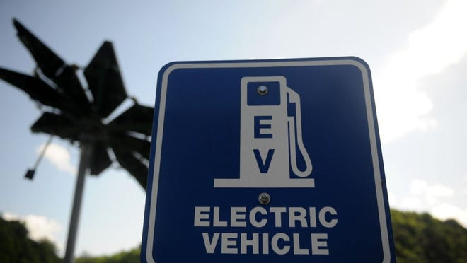 A sign designates an electric vehicle charging station at Melton Hill Campground outside Lenoir City on Friday. Behind the sign is a 'solar flare' which has solar panel leafs which tilt to accommodate the angle of the sun for maximum energy production. (CAITIE MCMEKIN/NEWS SENTINEL)