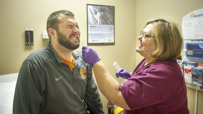 Medical Assistant Karen Whaley administers a flu test to Dustin Ellis Feb. 3 at the Summit Express Clinic in Fountain City. East Tennessee's flu season is just starting, and some doctors are seeing more people come in with flu symptoms. (PAUL EFIRD/NEWS SENTINEL)