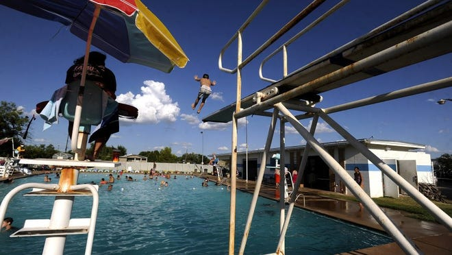 photos by Thomas Metthe/Reporter-News Hudson Womack, 8, leaps off the high dive at the Abilene Swim Club pool on July 30.