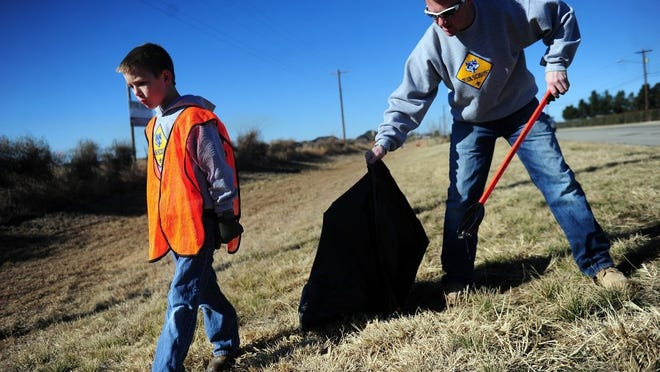 In a 2014 file photo Cameron Taylor, 8, and his father, Howard Taylor pick up trash at their site on Antilley Road. KAB recently won the Governor's Community Achievement Award for 2018, giving Abilene a $290,000 grant for beautification along state highway right-of-ways.