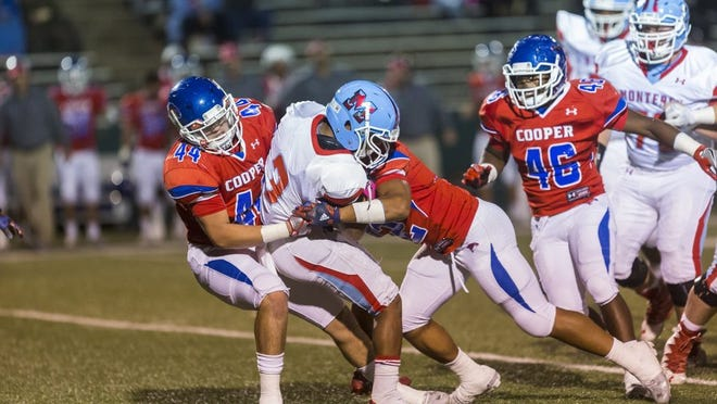 GARY RHODES/SPECIAL TO THE REPORTER-NEWS Cooper linebackers Richard Drew (left) and Actavius Lowry team up to take down Lubbock Monterey running back Zae Johnson during Cooper's 24-17 win Friday at Shotwell Stadium.