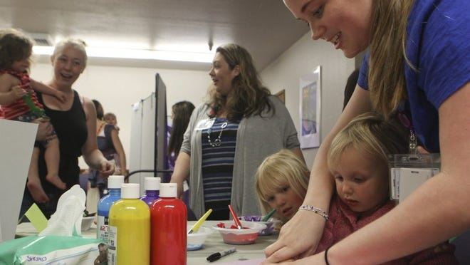 Greg Barnette/Record Searchlight Taylor Durfee, from right, helps Josephine Ballou, 2, and her sister Faith make hand prints Wednesday at the WIC office for the agency's grand opening.