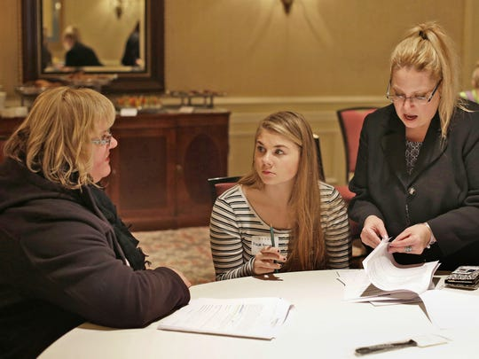 Kohler's Tracy Klein, senior HR generalist for Destination Kohler, far right, explains the application materials to Ursula Norwood, left, and her daughter Kaylee, 15, middle, during a job fair at The American Club Thursday March 10, 2016 in Kohler.