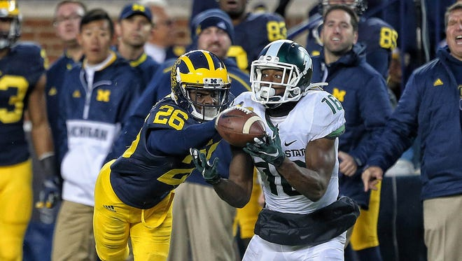 Michigan State wide receiver Aaron Burbridge (16) makes a catch against Michigan cornerback Jourdan Lewis (26) during the 2nd half of a game at Michigan Stadium on Oct. 17.