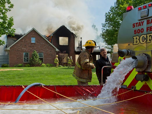Area firefighters battle a blaze in the 6000 block of Maderia Lane Friday, May 23, 2014, near Buck Creek. Multiple fire departments have been sent to help fight the fire. The home was totally destroyed.
