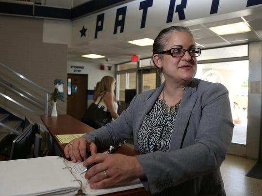 Principal, Bonnie King reviews a visitors log book at John Jay High School on May 9, 2018.