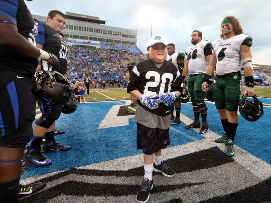 Honorary captain Colton Sheets walks on the field between MTSU and Charlotte players for the coin toss before Saturday's game in Murfreesboro. Sheets wears gloves that he got from a player when he visited practice Thursday.