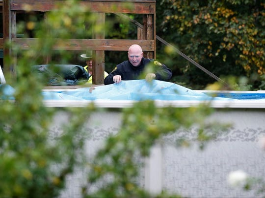 Law enforcement officers search a pool Wednesday near