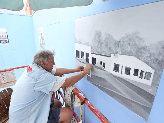 In 2015, Nationally known artist and Columbus Catholic High School graduate Gene Wesley works on one of the 20 murals that grace the walls of Hardacre Park