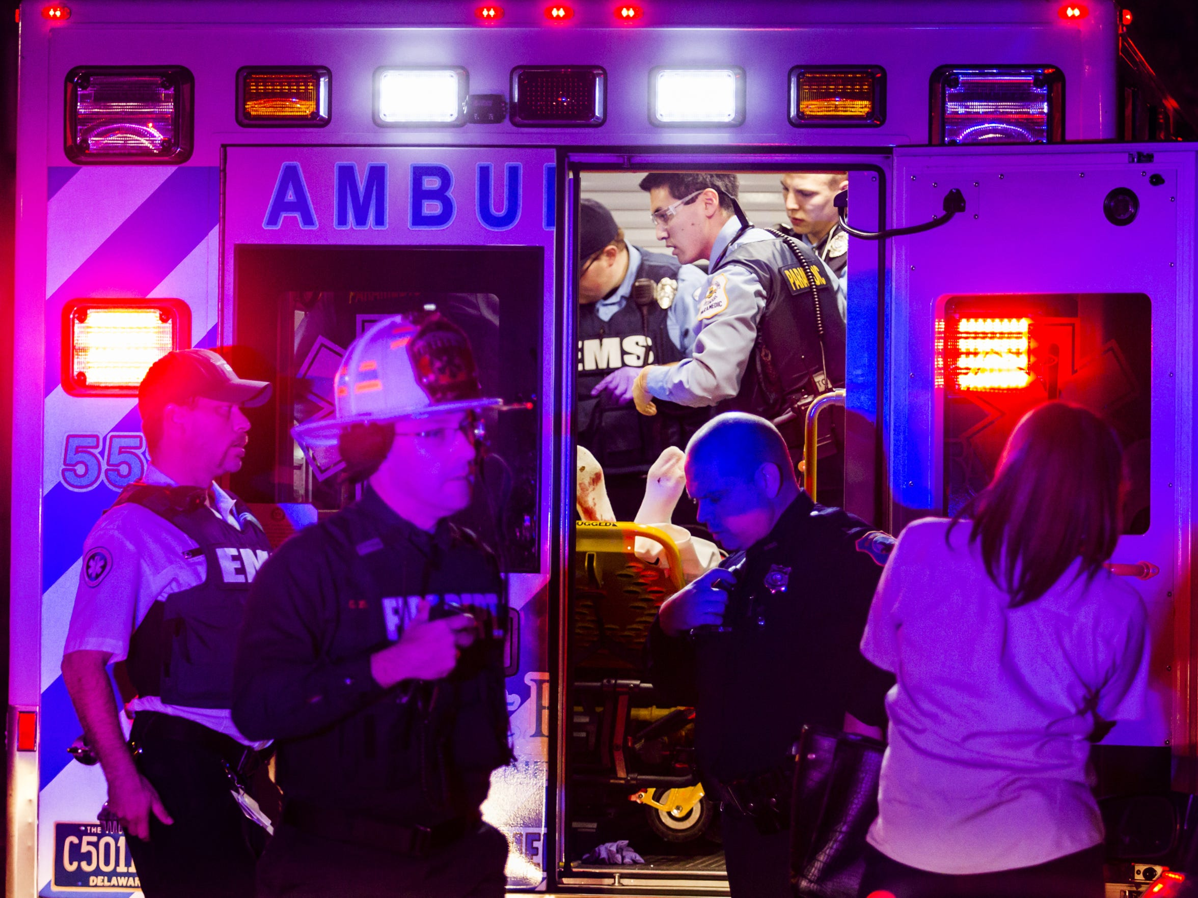 Emergency responders work on a person in an ambulance near the scene of a shooting on Taylor Street in Wilmington.
