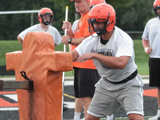 AJ Epenesa of Edwardsville battles the tackling dummy at practice in August, 2016 at the Edwardsville Sports Complex.