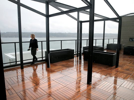 Property manager Victoria Luke with Spyglass Hill Apartments walks in the rooftop lounge area, which has views of Manette and the Bremerton waterfront.