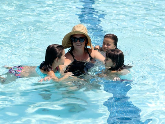 Adrianne Driscoll, center, swims Tuesday with her daughters Lucy, 6, from left, Emily, 3, and friend Evie Gagnon, 4, Tuesday at the Redding Aquatic Center.