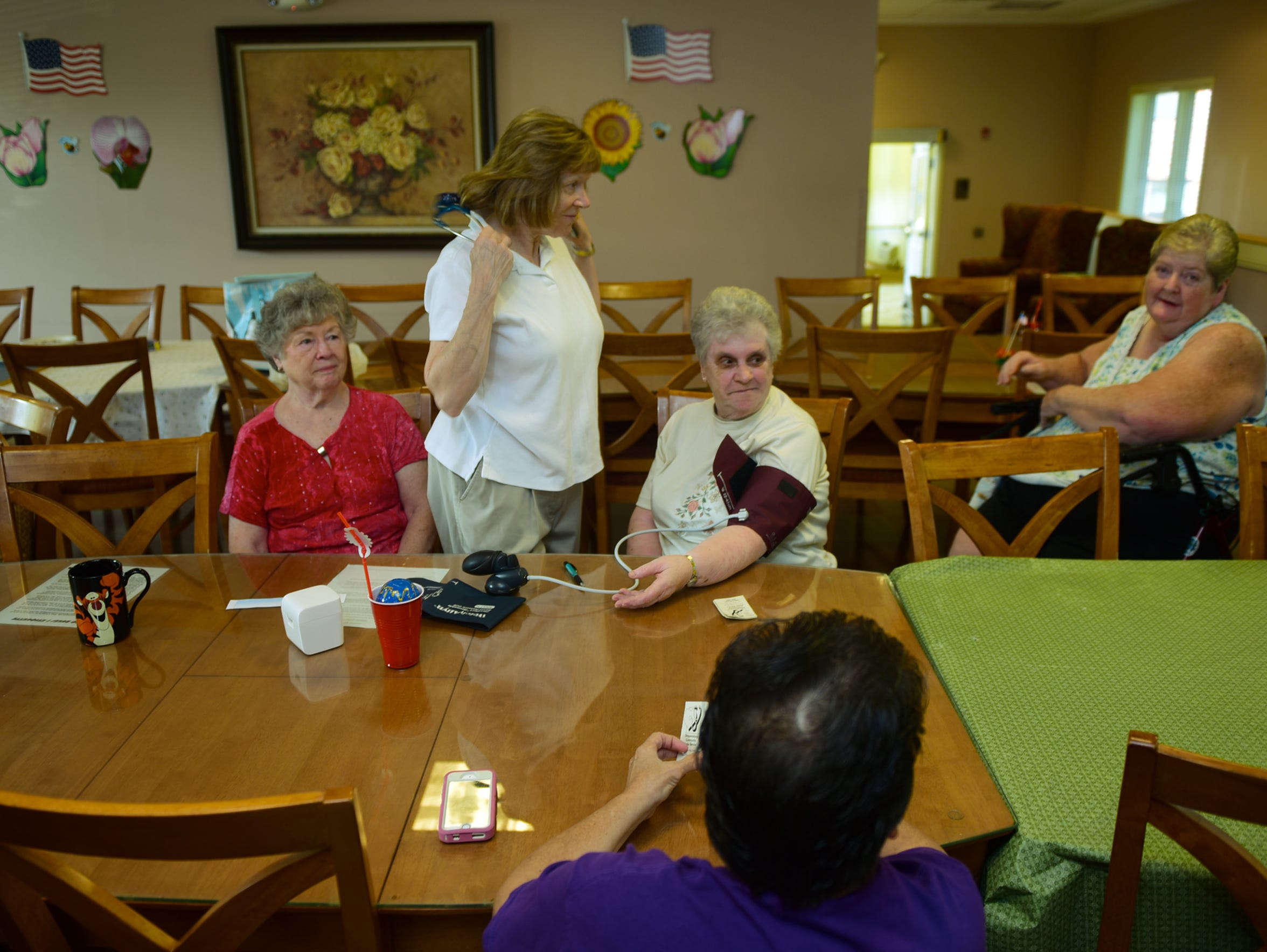 Community nurse Dee Parson, standing, visits residents