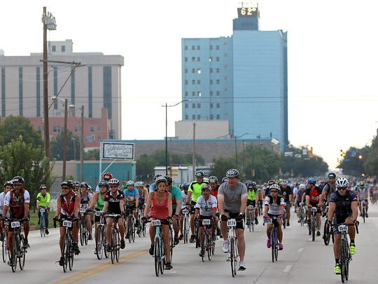 Riders move forward toward the starting line of the Hotter'N Hell as temperatures remained in the 60s and 70s for the start of the ride Saturday morning.