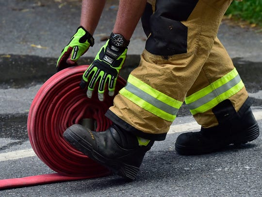 This July 2018 photo shows a firefighter rolling up a fire hose a the scene of a house fire in Guilford Township.