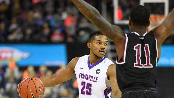 University of Evansville's Duane Gibson (25) looks for a teammate under defensive pressure from North Carolina Central's Alston Jones (11) as the University of Evansville play North Carolina Central for Kids Day at the Evansville Ford Center Monday, November 13, 2017.