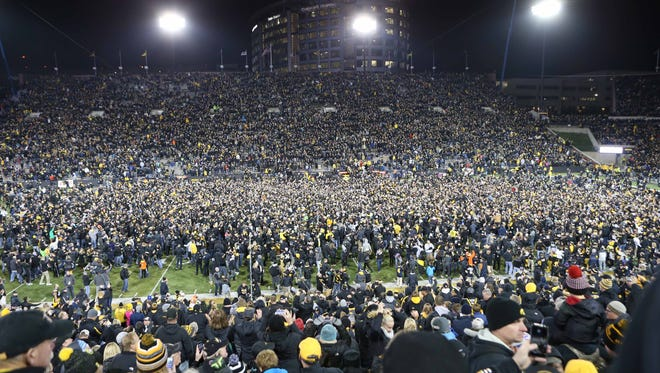 Iowa fans flood the field after the Hawkeyes upset Michigan.