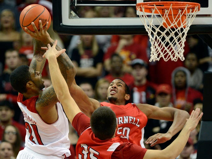 Louisville Cardinals forward Chane Behanan shoots against Cornell Big Red forwards Deion Giddens and Nenad Tomic (35) during the first half.