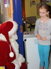 Maeve Leonard, 9, from Burlington, gets a visit from Santa on Wednesday at the UVM Children's Hospital.