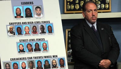 Morris County Prosecutor Fredric M. Knapp stands by Wednesday as New Jersey officials announced the takedown of a major international carjacking and stolen car trafficking ring that stole luxury cars from suburban communities in New Jersey as well as Rockland County in New York.