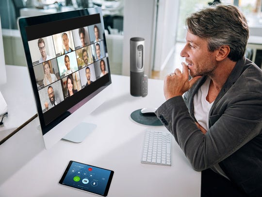 A man using Zoom on a computer to videoconference with other people
