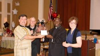 Photo is of Fr. Bambrick, Fr. Kimbowa, Jean Semler and Dave Thelen.
