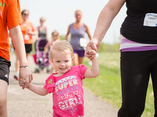 Birthday girl Shaley Gingras, 2, holds hands with Abby King, 10, left, and Crystal Gingras, all of Milton, at the annual VNA's Vermont Respite House 5K Fun Run & Jiggety Jog in Williston on Saturday.