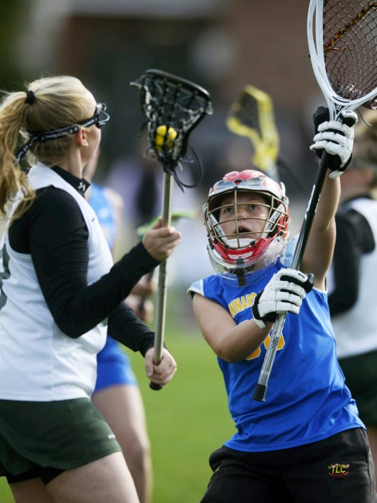 Kennard-Dale goalie Clare Boone, right, defends the net against York Catholic's Anna Linthicum during Tuesday's match at York Catholic. Boone posted 10 saves to help Kennard-Dale win, 16-14.
