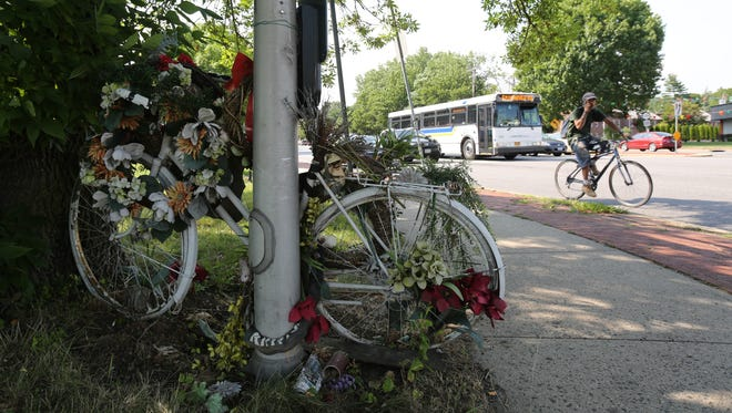 """A cyclist rides past a """"ghost bike"""" memorial for Merrill Cassell at the border of Greenburgh and the city of White Plains along Tarrytown Road, July 12, 2016."""