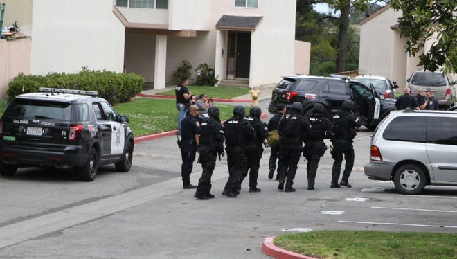 Salinas Police SWAT team enter an apartment off Acosta Plaza on Tuesday.
