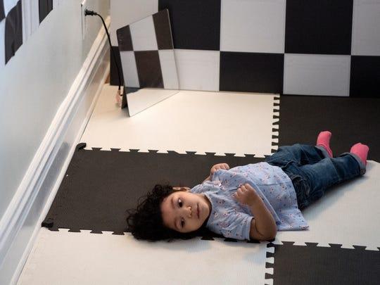 Darah, 1, nació con microcefalia causado por el virus del Zika. Darah acostada en un cuarto con diseños blancos y negros en el piso y las paredes, que su madre espera le ayude a fortalecer su visión, sábado 3 de marzo de 2018.