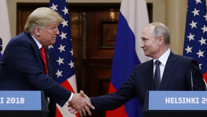 U.S. President Donald Trump, left, shakes hand with Russian President Vladimir Putin during a press conference after their meeting at the Presidential Palace in Helsinki, Finland on Monday.