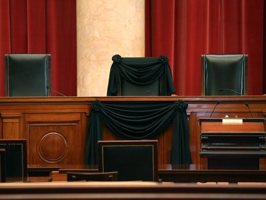 A black wool crepe cloth covers the bench where Justice