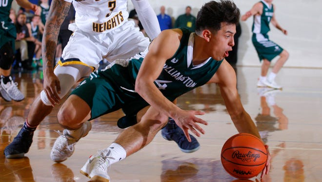 Williamston's Frankie Toomey, right, is pressured by Godwin Heights' Kelvyn Valdez during their MHSAA regional game Monday, March 13, 2017, in Ionia, Mich. Williamston won 69-65..